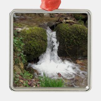 Ornement Carré Argenté Peu de cascade par les roches moussues dans la