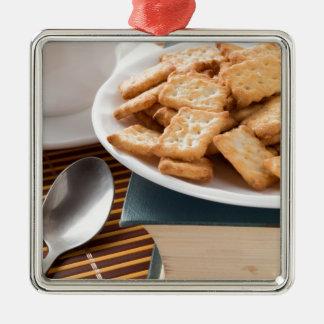 Ornement Carré Argenté Plat blanc avec des biscuits sur le vieux livre