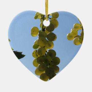 Ornement Cœur En Céramique Raisins blancs sur la vigne contre le ciel bleu