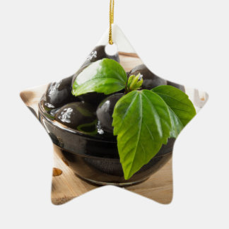 Ornement Étoile En Céramique Olives noires sur une table et des tasses en verre