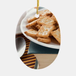 Ornement Ovale En Céramique Plat blanc avec des biscuits sur le vieux livre