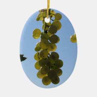 Ornement Ovale En Céramique Raisins blancs sur la vigne contre le ciel bleu