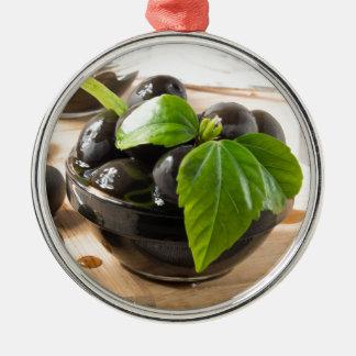 Ornement Rond Argenté Olives noires sur une table et des tasses en verre