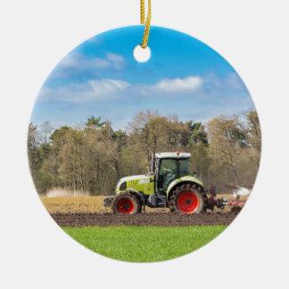 Ornement Rond En Céramique Agriculteur sur le tracteur labourant le sol