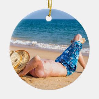 Ornement Rond En Céramique Jeune prendre un bain de soleil de touristes sur
