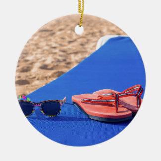 Ornement Rond En Céramique Pantoufles et lunettes de soleil sur le lit pliant