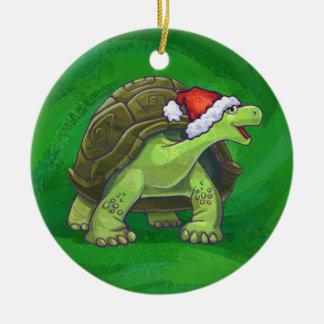 Ornement Rond En Céramique Tortue dans le casquette de Père Noël sur le vert