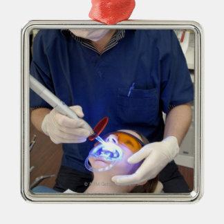 Orthodontiste employant la lumière UV pour placer Ornement Carré Argenté
