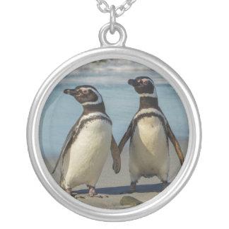 Paires de pingouins sur la plage pendentif rond