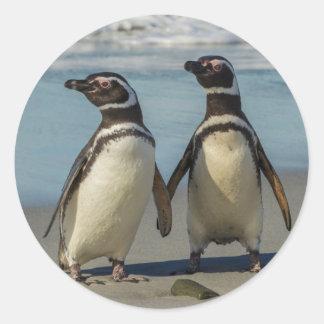 Paires de pingouins sur la plage sticker rond