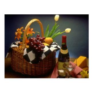 Panier jaune de pique-nique avec du vin, fromage, carte postale