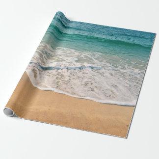 Papier Cadeau Plage sablonneuse à midi avec l'eau bleue et le