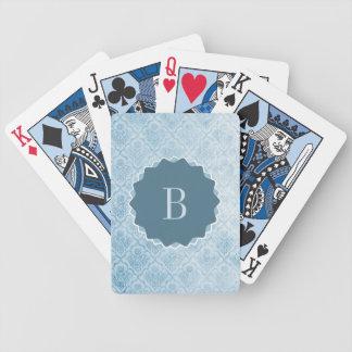 Papier peint vintage bleu décoré d'un monogramme jeux de cartes