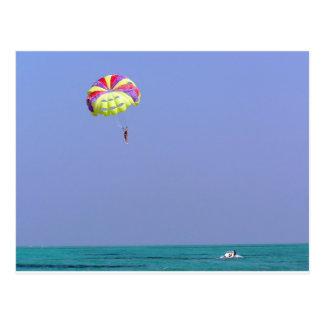 Parachute ascensionnel au-dessus de l'eau bleue carte postale