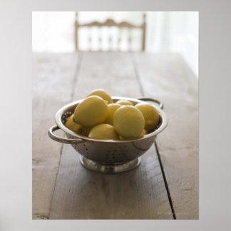 Passoire avec des citrons sur la table en bois poster