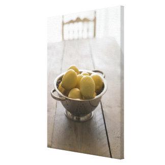 Passoire avec des citrons sur la table en bois toiles