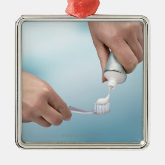 Pâte dentifrice étant serrée sur une brosse ornement carré argenté