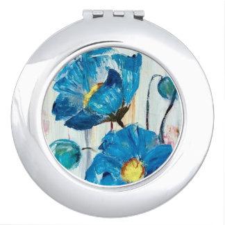 Pavots bleus sur le miroir compact