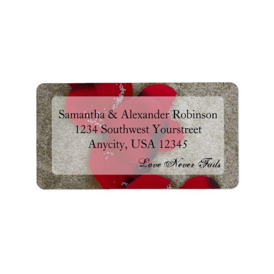 Pétales de rose rouges sur le mariage de plage de étiquette d'adresse