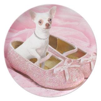 Petit chiwawa dans des chaussures girly roses avec assiette