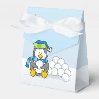 Petit pingouin se reposant avec des boules de boites de faveur