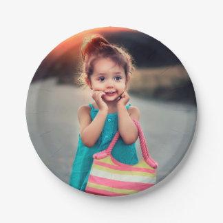 Petite fille avec le sac à main rayé assiettes en papier