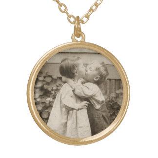 Photo vintage d'amour des enfants embrassant dans collier plaqué or