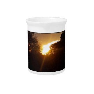 Pichet Lever de soleil brillant au-dessus des arbres