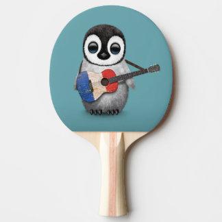 Pingouin de bébé jouant le bleu français de raquette de ping pong