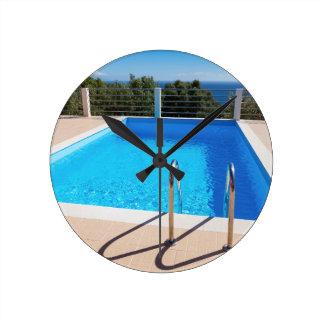 Piscine bleue avec des étapes en mer horloge ronde