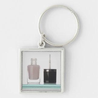 Plan rapproché d'une bouteille de vernis à ongles porte-clé carré argenté