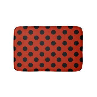 Pois noir sur le rouge tapis de bain