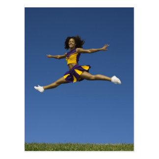 Pom-pom girl femelle faisant des fentes de saut en carte postale