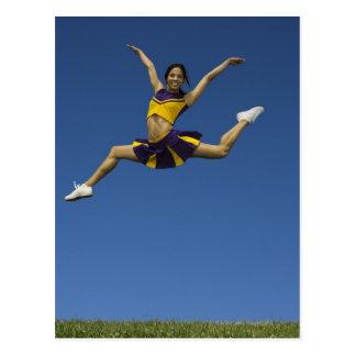 Pom-pom girl femelle sautant en air, bras carte postale