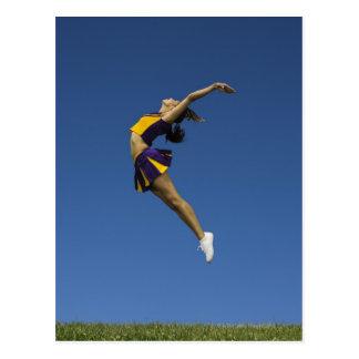 Pom-pom girl femelle sautant en air, vue de côté carte postale