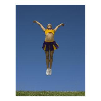 Pom-pom girl femelle sautant en air, vue de face carte postale