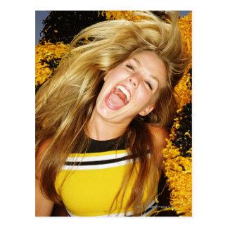 Pom-pom girl renversant des cheveux, riant, carte postale