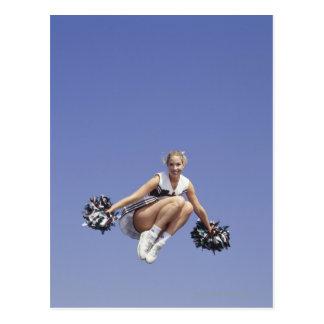 Pom-pom girl sautant, vue d'angle faible, portrait carte postale