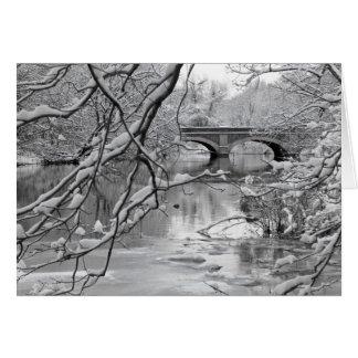Pont de voûte au-dessus de rivière congelée en carte de vœux