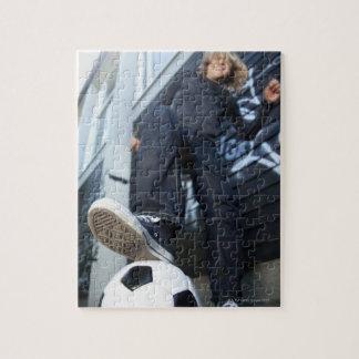 portrait d'angle faible de garçon blond avec le puzzle