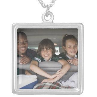 Portrait des enfants de sourire dans la voiture pendentif carré