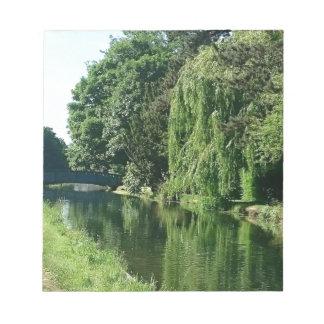 Promenade ensoleillée verte de rivière d'arbres de blocs notes