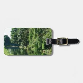 Promenade ensoleillée verte de rivière d'arbres de étiquettes bagages
