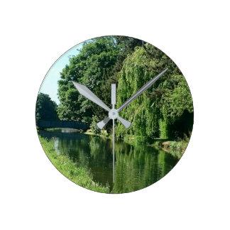 Promenade ensoleillée verte de rivière d'arbres de horloge ronde
