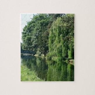 Promenade ensoleillée verte de rivière d'arbres de puzzle