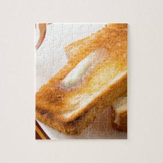 Puzzle Pain grillé chaud avec du beurre sur un plan