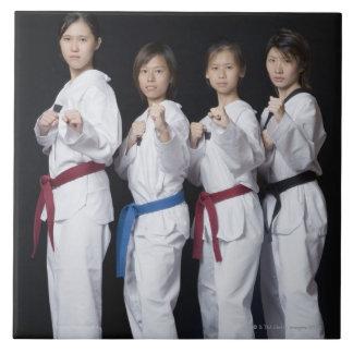Quatre jeunes femmes se tenant en position de poin carreaux en céramique