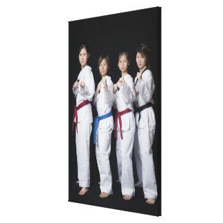 Quatre jeunes femmes se tenant en position de poin toile tendue sur châssis