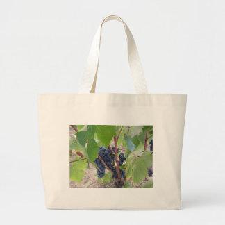 Raisins rouges sur la vigne avec le feuille vert grand tote bag