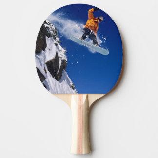 Raquette De Ping Pong Homme sur un surf des neiges sautant outre d'une